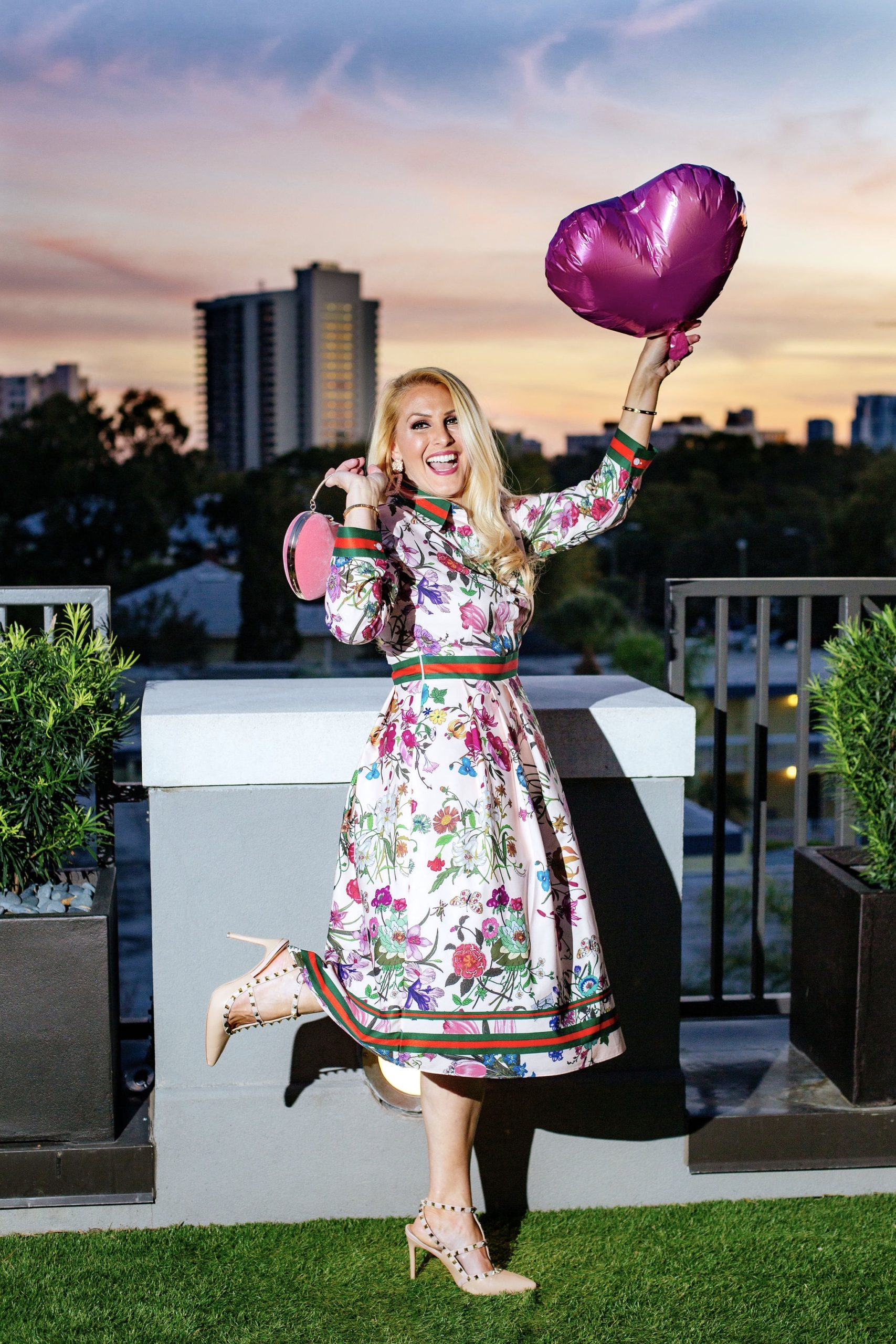 Jenn Truman Fashion and Style Blogger @jtstjtst11 is standing with one leg kicked back admiring the beautiful sunset skyline at Edge Rooftop Cocktail Lounge Epicurean Hotel, Autograph Collection. She is wearing a pink floral dress from amazon fashion and nude studded heels from amazon. She's holding a pink heart ballon in one hand and a pink heart purse in the other.