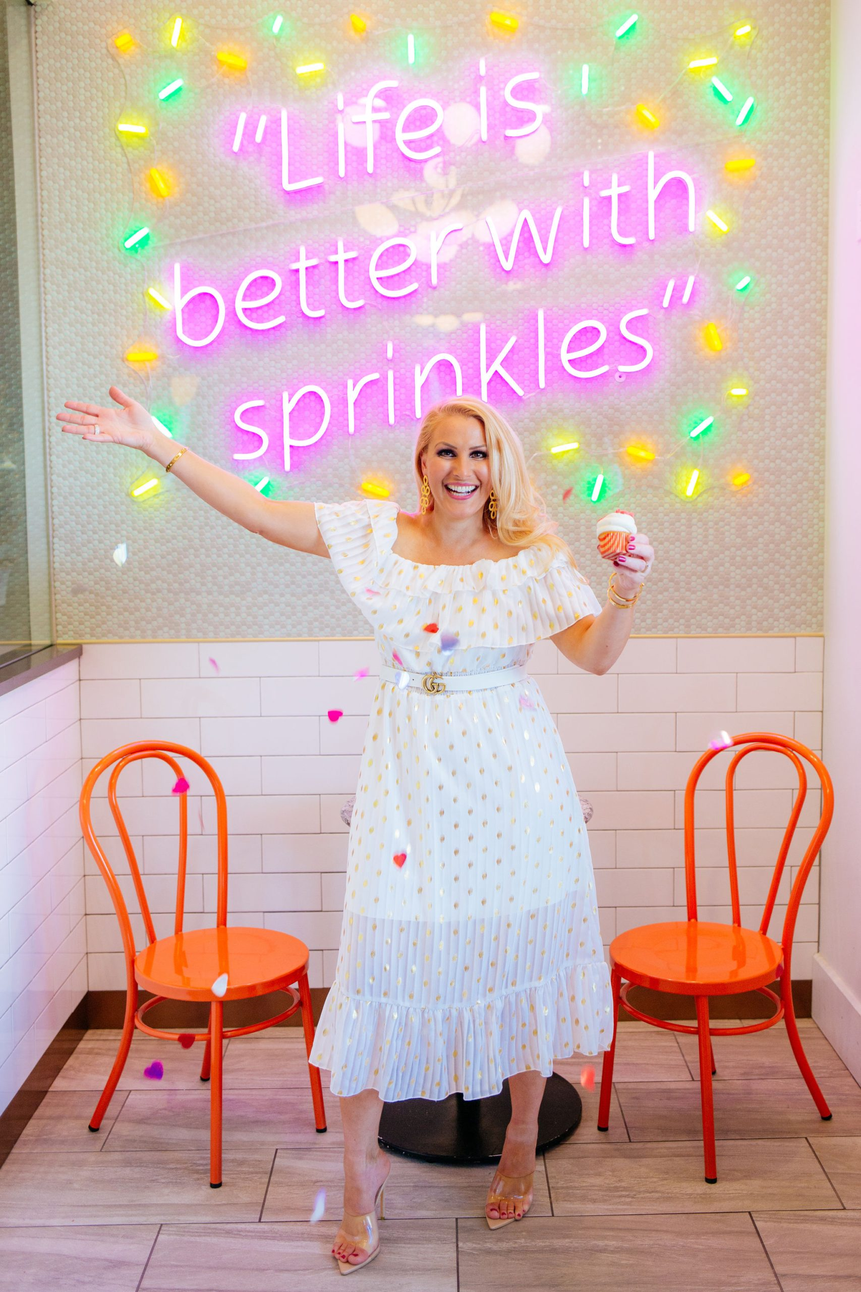 Tampa Fashion blogger Jenn Truman @jtstjtst11 is holding a cupcake and throwing heart confetti as she stands in from of the lit sign that says Life is Better with Sprinkles. She is wearing a white off the shoulder dress with gold dots from Amazon fashion, clear heels and Gold Lisi Lerch earrings.