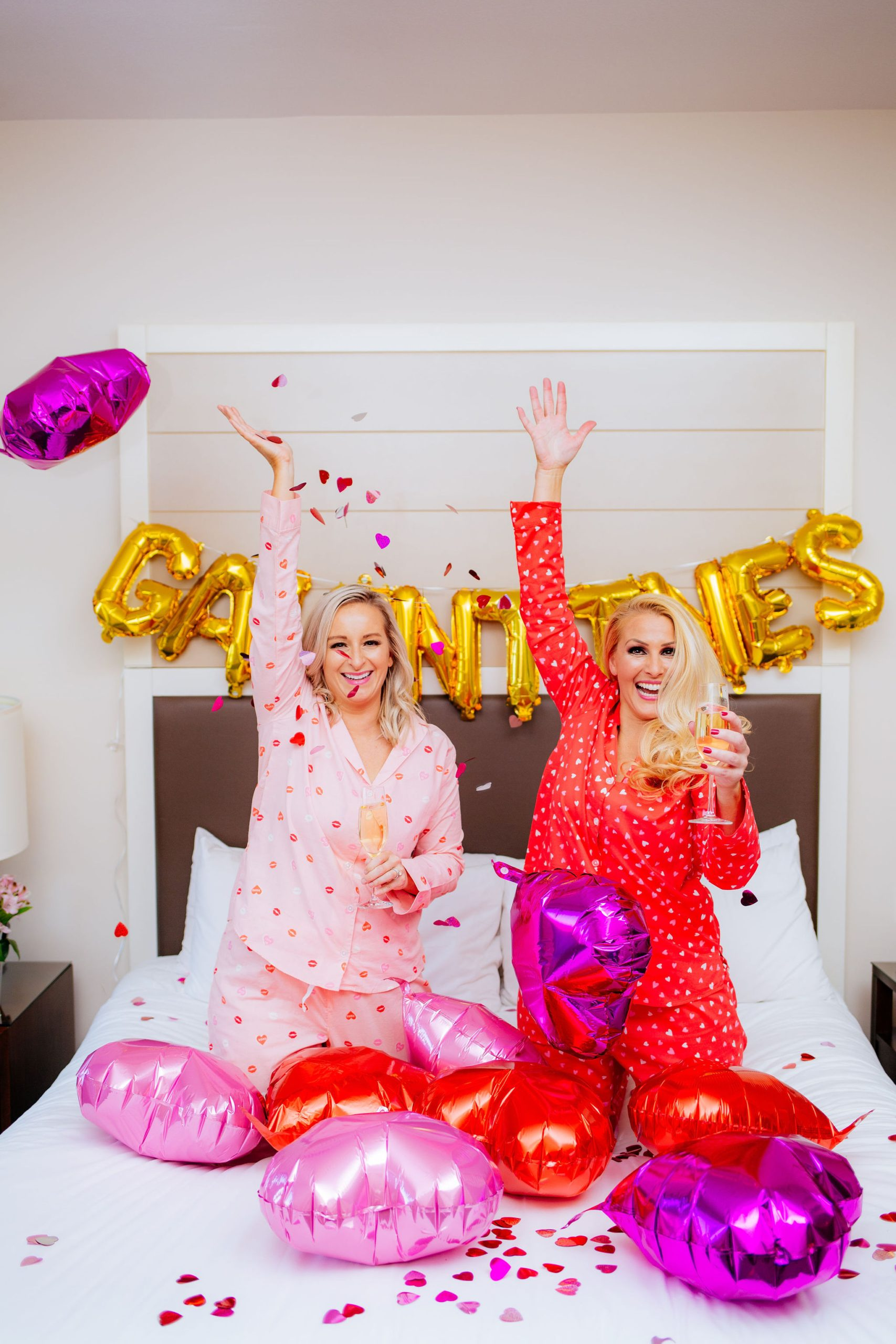 Tampa Fashion Bloggers Jenn Truman @jtstjtst11 and Jill DiGioia at the Epicurean Hotel, Autograph Collection in their room in pink and red Old Navy Valentine's day pajamas. They are throwing heart confetti and drinking chamgange.