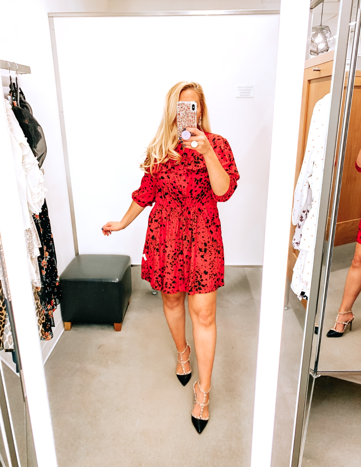 Tampa Blogger Jenn Truman providing a mirror selfie inside Nordstrom at Tampa International Plaza. She is wearing a TOPSHOP Animal Print Tie Waist Mini Shirtdress from Nordstrom and Valentino dupe black studded heels from Amazon. She is holding her phone for a mirror selfie.