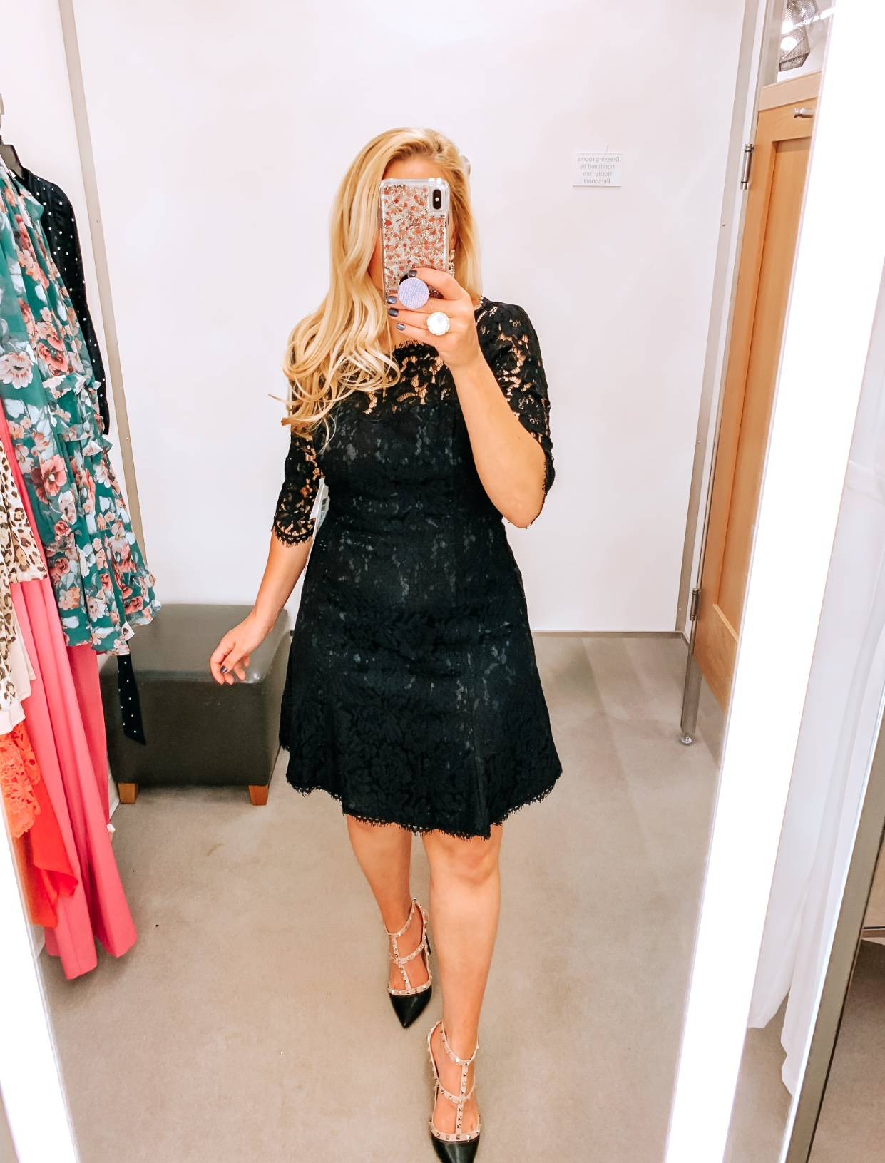 Tampa Blogger Jenn Truman providing a mirror selfie inside Nordstrom at Tampa International Plaza. She is wearing an Eliza J black Lace Fit and flare cocktail dress from Nordstrom and Valentino dupe black studded heels from Amazon. She is holding her phone for a mirror selfie try on session.
