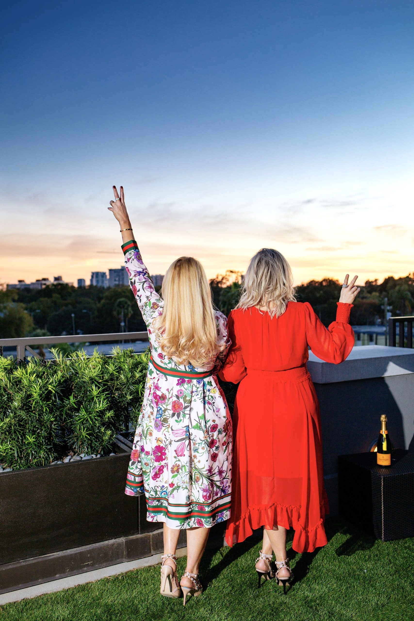 Jenn Truman Fashion and Style Blogger @jtstjtst11 is standing admiring the beautiful sunset skyline at Edge Rooftop Cocktail Lounge Epicurean Hotel, Autograph Collection. She is wearing a pink floral dress from amazon fashion and nude studded heels from amazon. She's holding the peace sign up with her first two fingers admiring the sunset.
