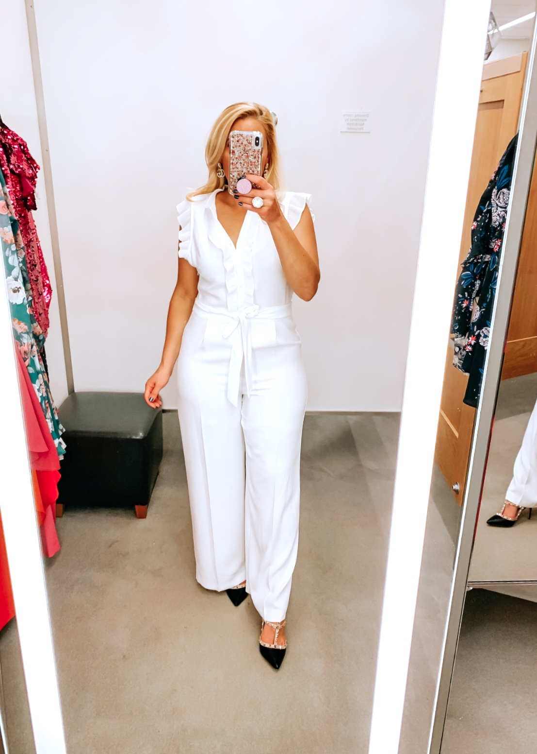 Tampa Blogger Jenn Truman providing a mirror selfie inside Nordstrom at Tampa International Plaza. She is wearing a CECE white jumpsuit from Nordstrom and Valentino dupe black studded heels from Amazon. She is holding her phone for a mirror selfie.