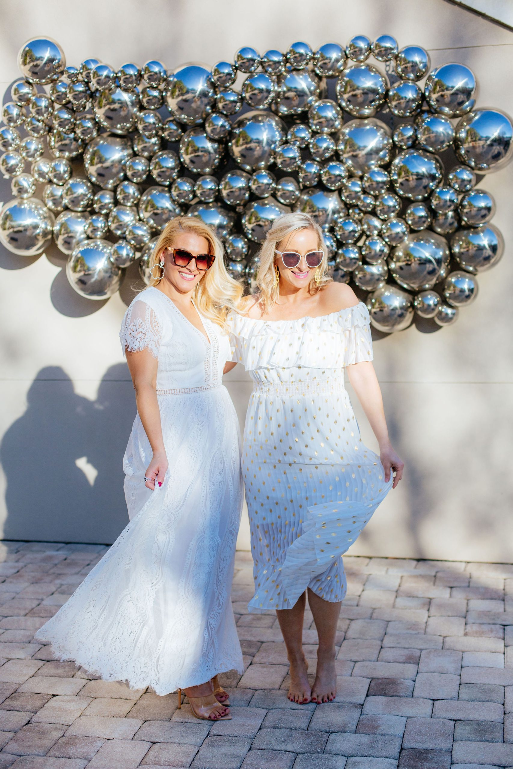 Style Blogger Jenn Truman @jtstjtst11 at the Epicurean Hotel, Autograph Collection poolside and in a bohemian white lace dress with clear heels and sunglasses on. She's also wearing silver bamboo Lisi Lerch earrings