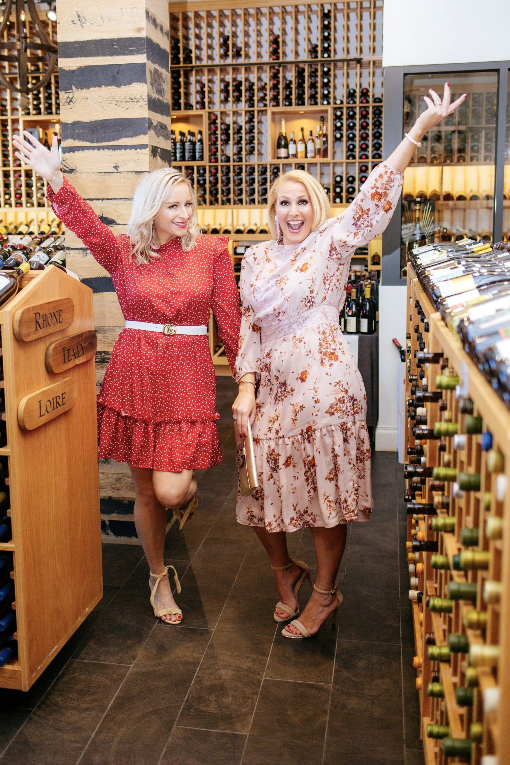Jenn Truman Tampa Fashion Blogger @jtstjtst11 at Bern's Fine Wines and Spirits standing with her hands in the air showcasing all of the wine options in the store. She's in a pink floral mock neck floral dress from Target. She's holding a Tory Burch gold clutch in one hand and has a smile on her face. She's also wearing pink statement earrings from Lisi Lerch.